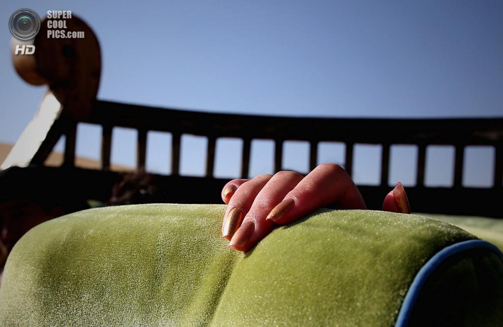 Китай. Ордос, Внутренняя Монголия. 20 июля. Путешественница в открытом туристическом автобусе катается по дюнам. (Feng Li/Getty Images)