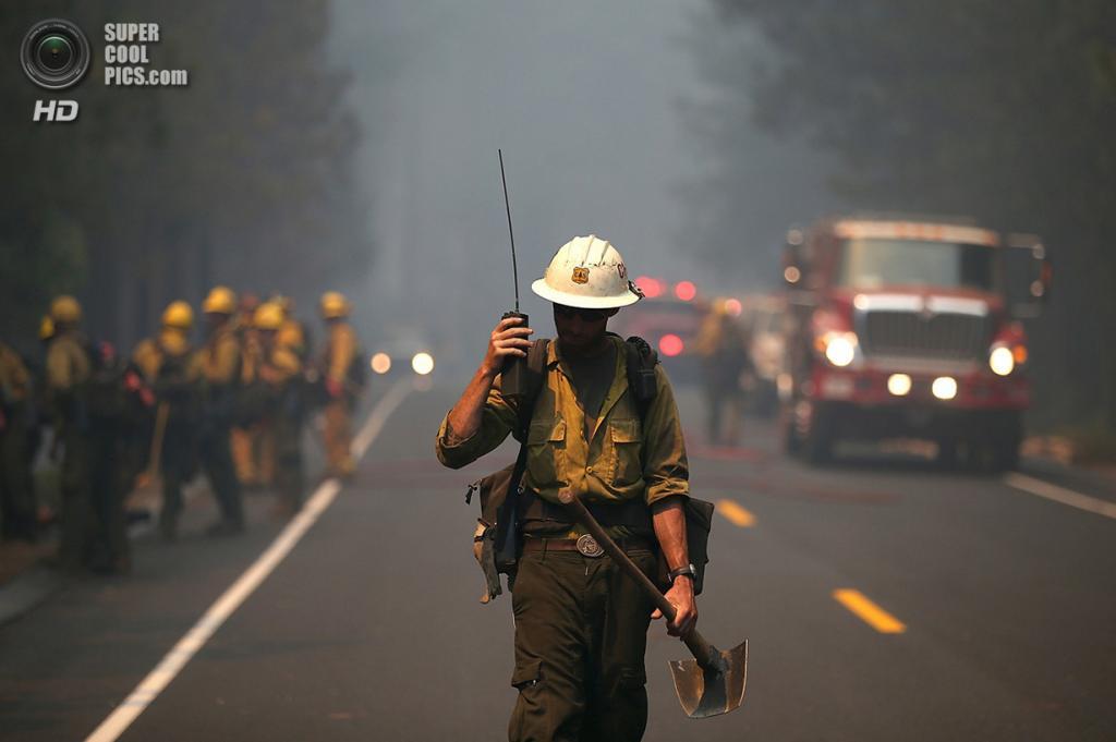 США. Гровленд, Калифорния. 22 августа. Пожарный слушает инструкции по рации. (Justin Sullivan/Getty Images)