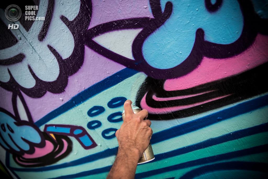 США. Нью-Йорк. 9 августа. Уличный художник Стив Лью, работающий под псевдонимом Kidlew, рисует граффити на стене здания 5 Pointz в районе Лонг-Айленд-Сити в Куинсе, которое собираются снести для строительства жилых многоэтажек. (ANDREW BURTON/AFP/Getty Images)
