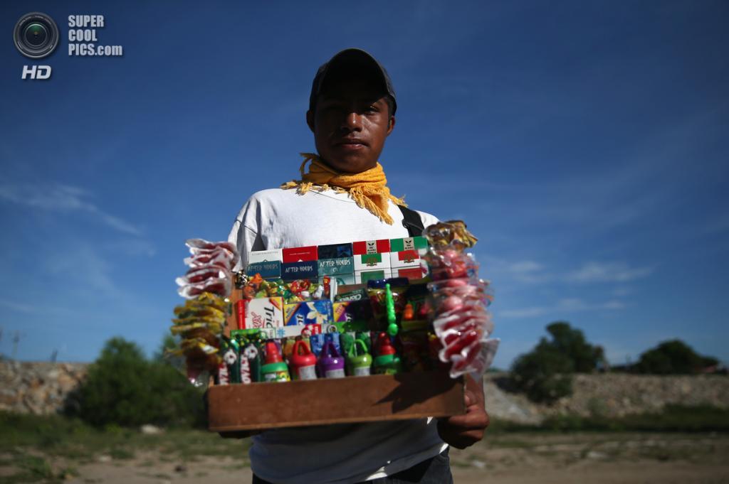 Мексика. Сьюдад-Идальго, Чьяпас. 2 августа. Хорхе Эрнандес из Гватемалы продаёт конфеты и сигареты на мексиканской стороне реки Сучьяте. (John Moore/Getty Images)