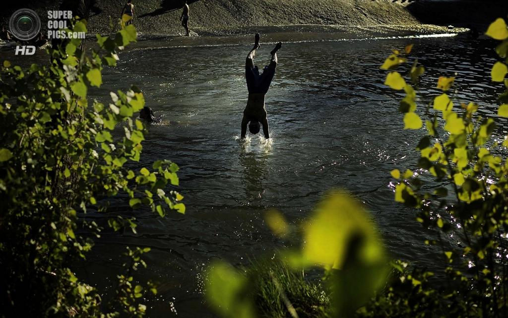 Испания, Памплона, Наварра. Испанец охлаждается в реке Арга. (AP Photo/Rajesh Kumar Singh)