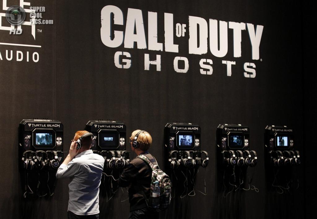 Германия. Кёльн, Северный Рейн — Вестфалия. 21 августа. Посетители Gamescom 2013 оценивают возможности новой гарнитуры Turtle Beach у стенда «Call of Duty: Ghosts», для которой она наверняка пригодится. (REUTERS/Ina Fassbender)