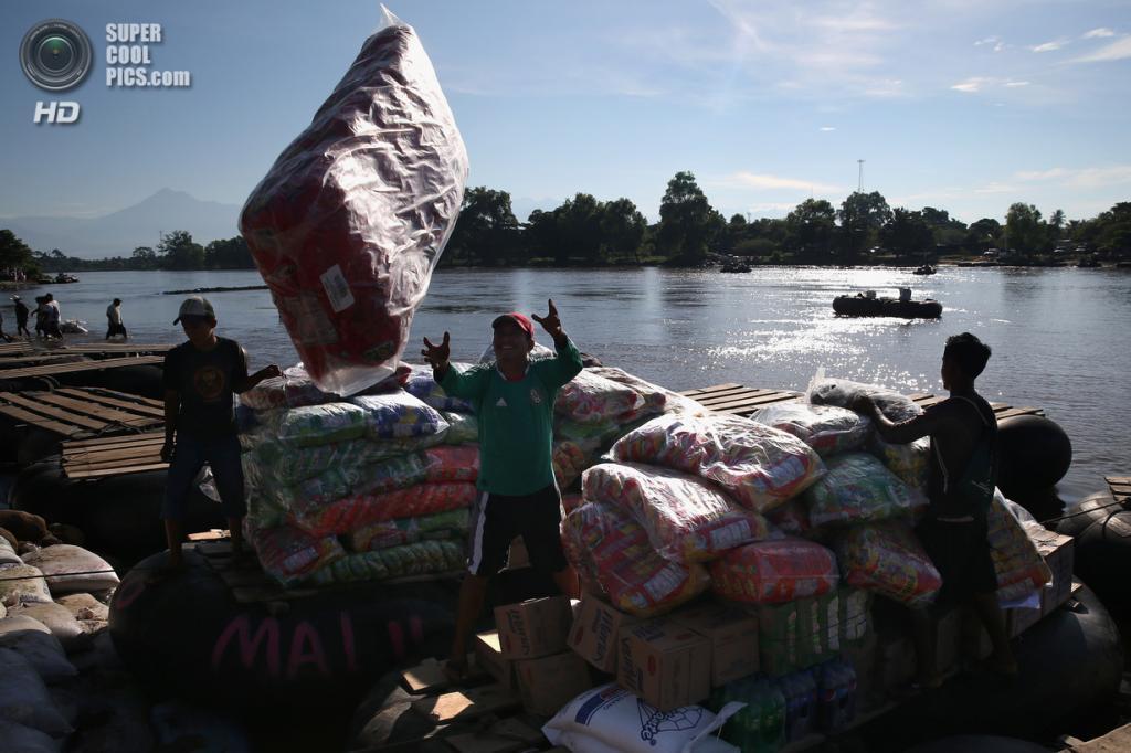 Мексика. Сьюдад-Идальго, Чьяпас. 2 августа. Гватемальские торговцы выгружают плот с товарами, нелегально провезёнными через границу. (John Moore/Getty Images)