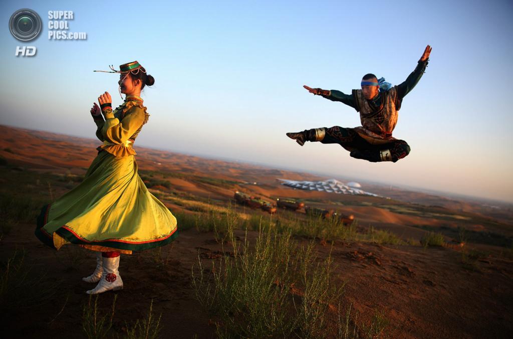 Китай. Ордос, Внутренняя Монголия. 19 июля. Танцоры в костюмах с монгольскими мотивами репетируют на фоне гостиницы Desert Lotus Hotel. (Feng Li/Getty Images)