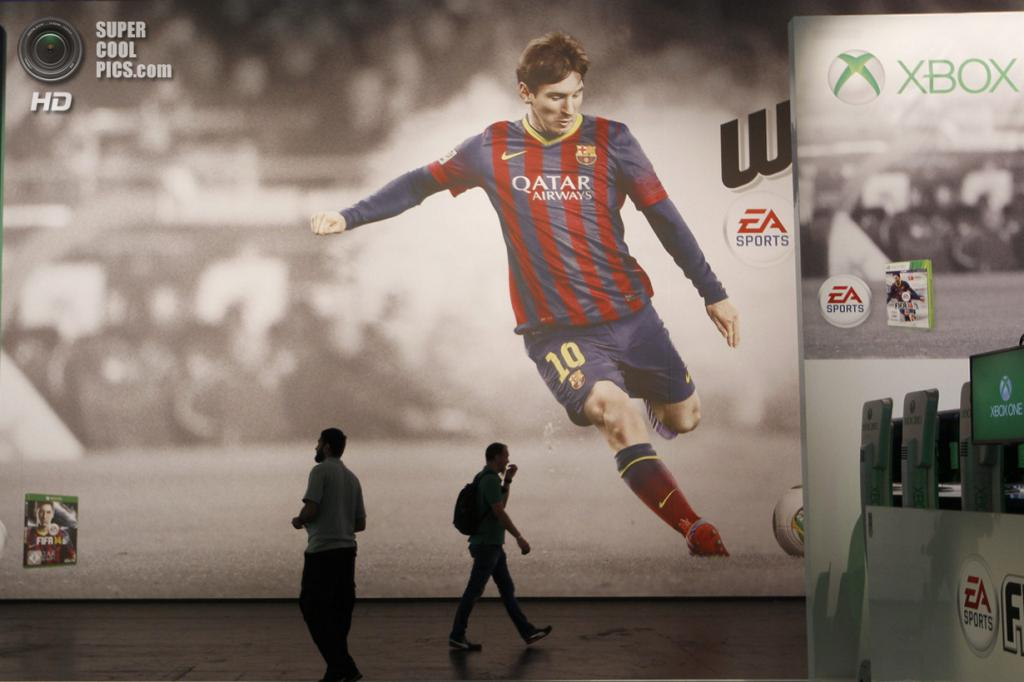 Германия. Кёльн, Северный Рейн — Вестфалия. 21 августа. Плакат с Лионелем Месси, который, такое впечатление, собирается сбить проходящих мимо посетителей стенда «FIFA 14», как кегли. (REUTERS/Ina Fassbender)