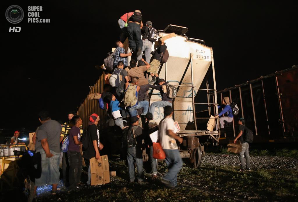 Мексика. Арриага, Чьяпас. 4 августа. Гватемальские нелегальные иммигранты влазят на грузовой поезд, направляющийся на север. (John Moore/Getty Images)