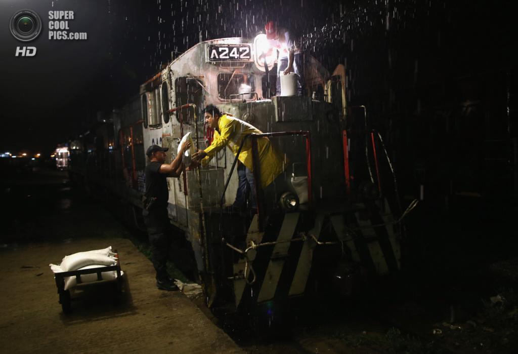Мексика. Арриага, Чьяпас. 4 августа. Поездная бригада заправляет двигатель песком, чтобы разбрасывать его на скользкий от дождя рельсовый путь. (John Moore/Getty Images)