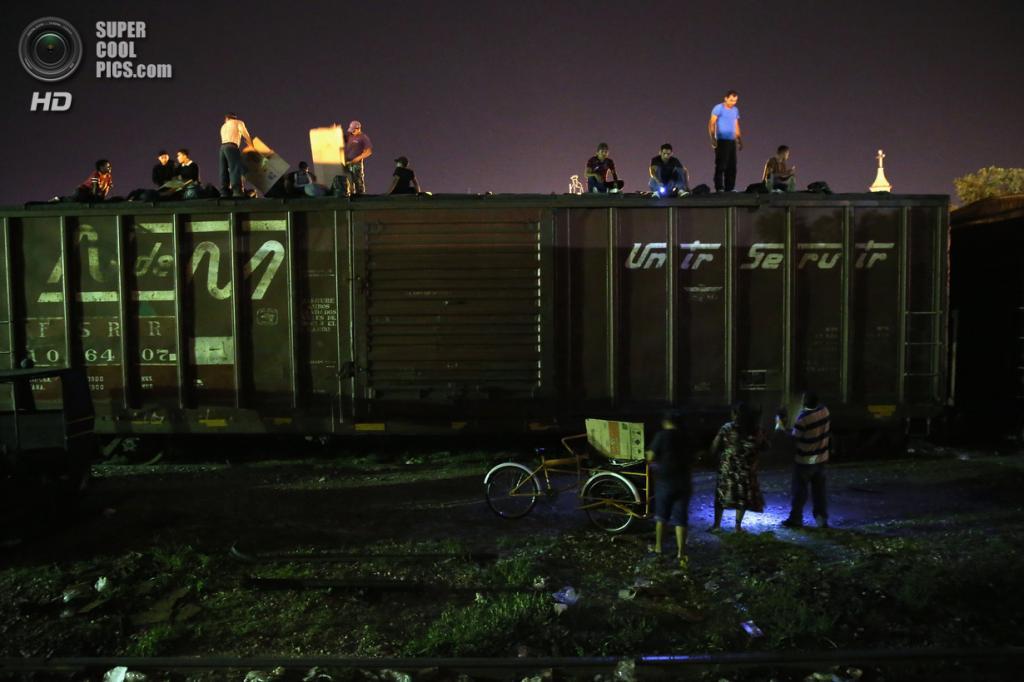 Мексика. Арриага, Чьяпас. 4 августа. Гватемальские нелегальные иммигранты верхом на грузовом поезде, направляющемся на север, во время грозы. (John Moore/Getty Images)