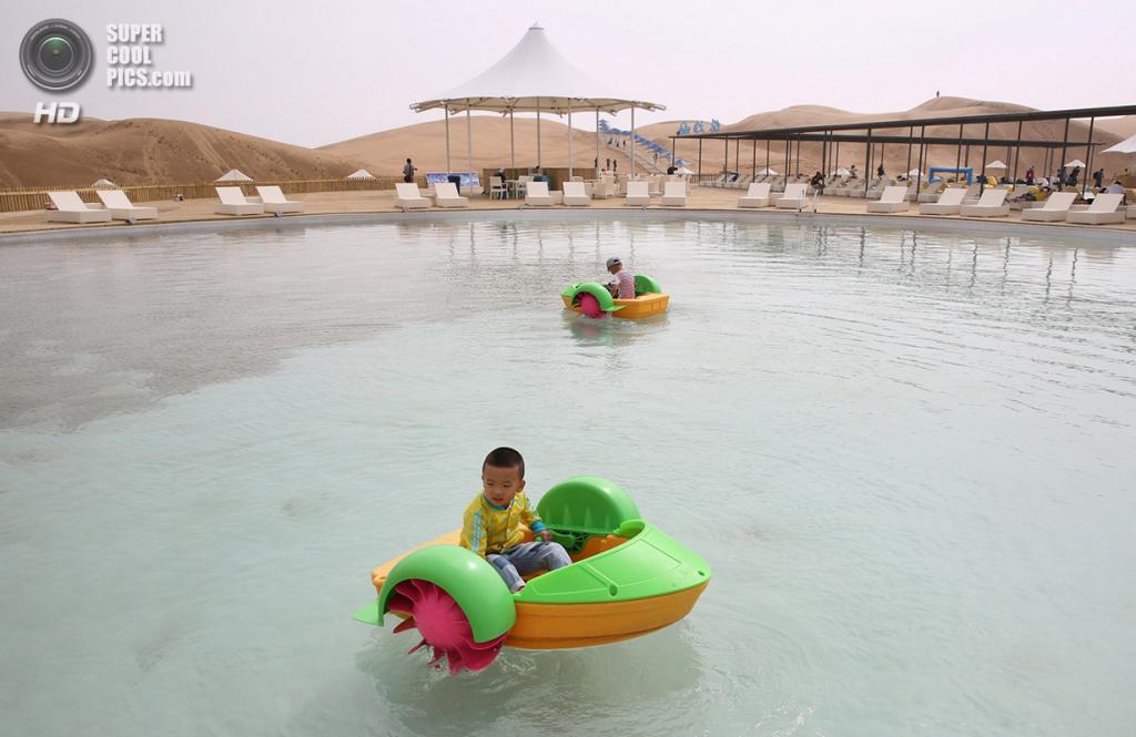 Китай. Ордос, Внутренняя Монголия. 18 июля. Мальчики катаются на игрушечных лодках по бассейну. (Feng Li/Getty Images)