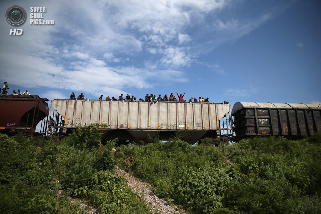 Мексика. Сьюдад-Истепек, Оахака. 4 августа. Гватемальские нелегальные иммигранты верхом на грузовом поезде, направляющемся на север. (John Moore/Getty Images)