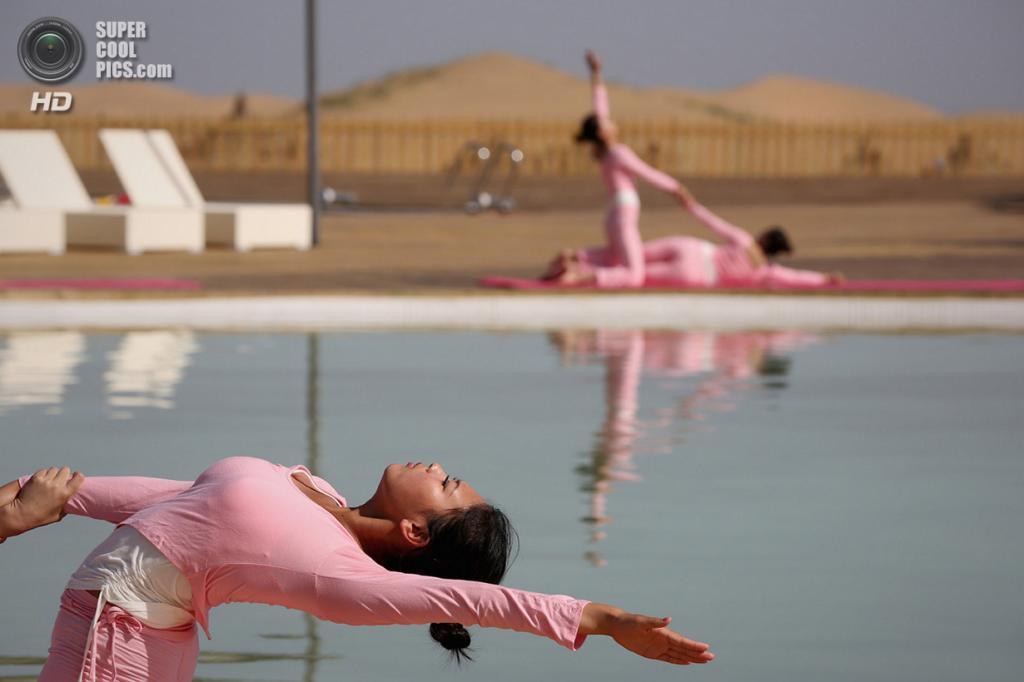 Китай. Ордос, Внутренняя Монголия. 20 июля. Занятия йогой у бассейна. (Feng Li/Getty Images)