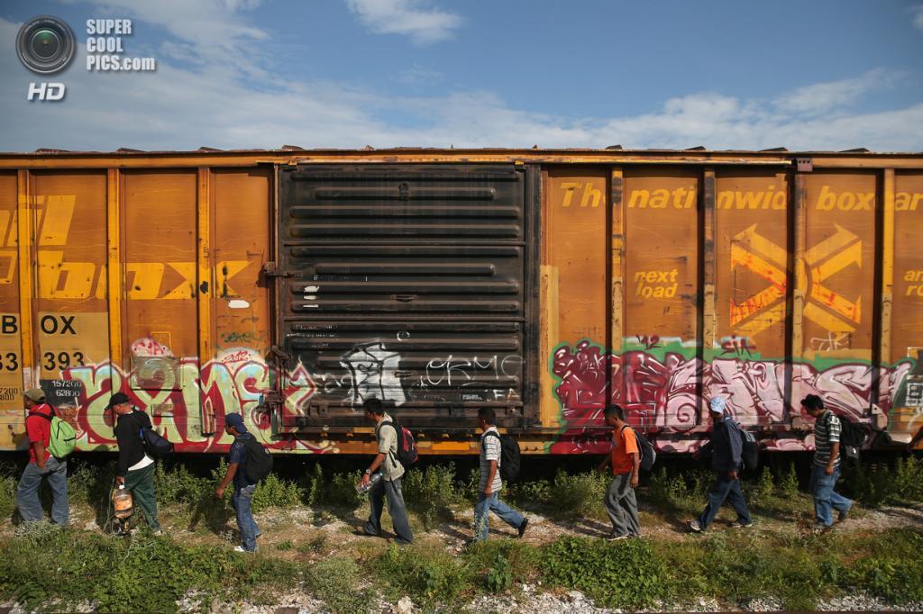 Мексика. Сьюдад-Истепек, Оахака. 4 августа. Гватемальские нелегальные иммигранты слазят с грузового поезда после 15-часовой поездки на его крыше, чтобы перекусить. (John Moore/Getty Images)