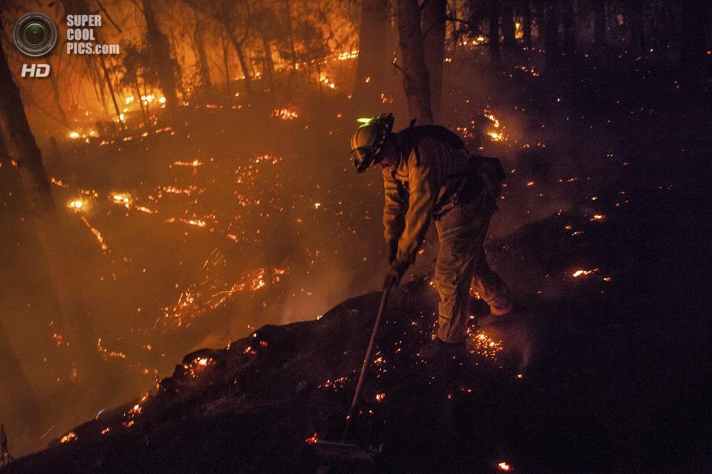 США. Бак-Медоус, Калифорния. 22 августа. Пожарный Дэйв Бек разгребает угли подальше от дороги. (REUTERS/Max Whittaker)