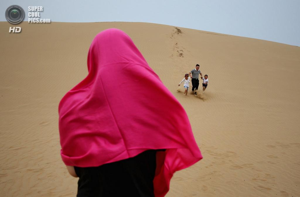 Китай. Ордос, Внутренняя Монголия. 21 июля. Путешествующая семья сбегает с песчаной дюны, генерируя странный ревущий звук — природный феномен, до сих пор толком не исследованный наукой. (Feng Li/Getty Images)