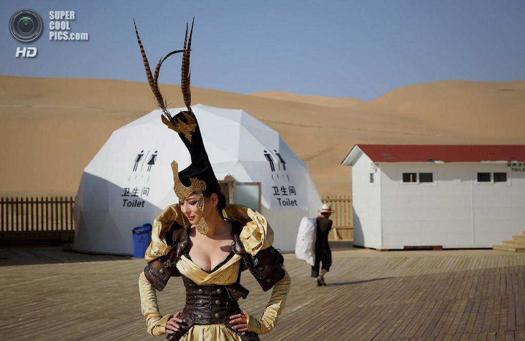 Китай. Ордос, Внутренняя Монголия. 18 июля. Модель, одетая в костюм с монгольскими мотивами, готовится к показу мод. (Feng Li/Getty Images)