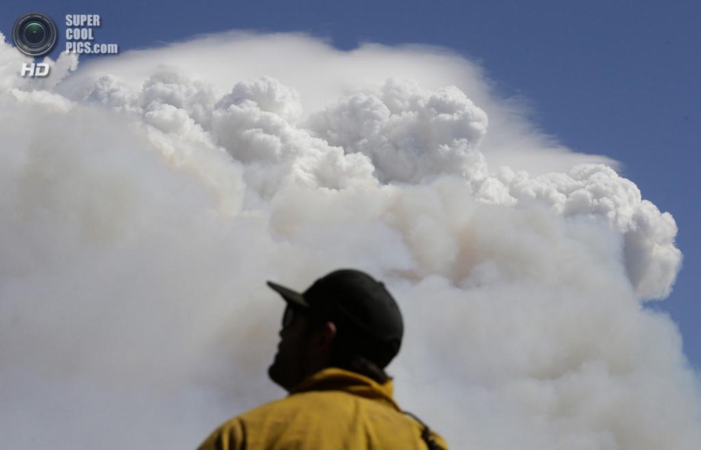 США. Гровленд, Калифорния. 25 августа. Пожарный Чарли Феррис из Лос-Анджелеса на фоне дымового шлейфа от лесного пожара «Rim Fire». (AP Photo/Jae C. Hong)
