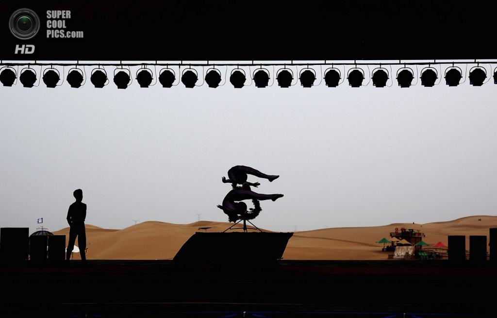 Китай. Ордос, Внутренняя Монголия. 21 июля. Выступление акробатов. (Feng Li/Getty Images)