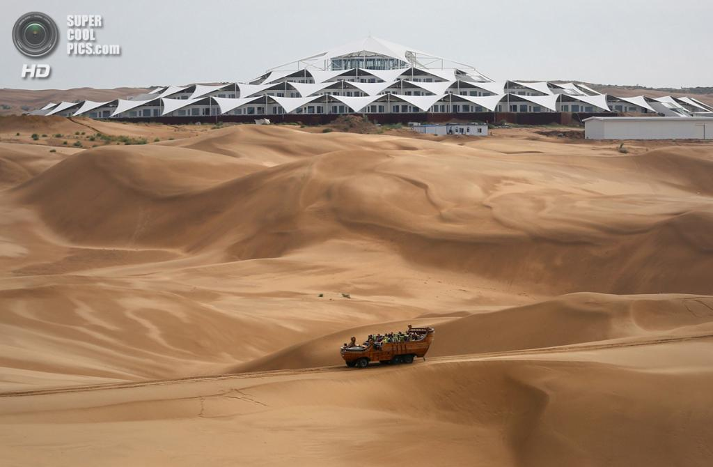 Китай. Ордос, Внутренняя Монголия. 17 июля. Туристы путешествуют по дюнам на фоне гостиницы Desert Lotus Hotel. (Feng Li/Getty Images)
