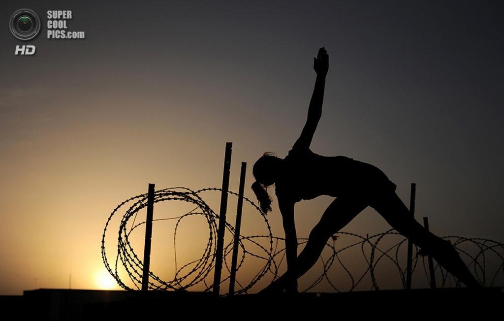 Афганистан. Гильменд. 3 июня 2009 года. Британский капрал Сандра Джордан упражняется на рассвете. Джордан находится под опекой медсестёр в лагерной больнице. (AP Photo/Jon Bevan, Ministry of Defence)