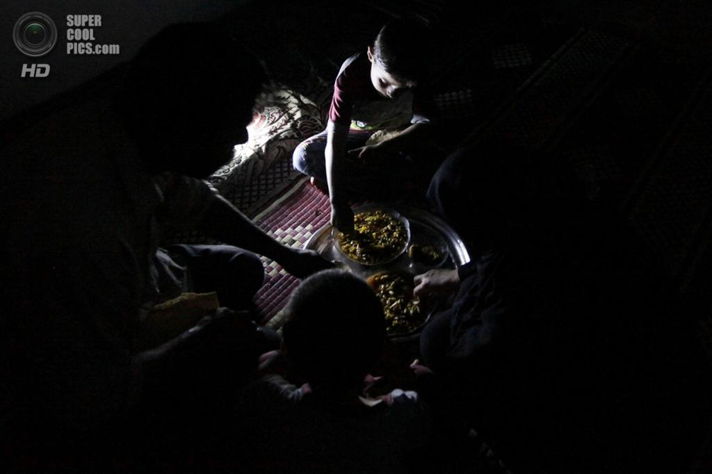Исса ужинает с семьёй в скромном жилище расположенном на территории оружейного завода в Алеппо. (Foto Reuters / Hamid Khatib)