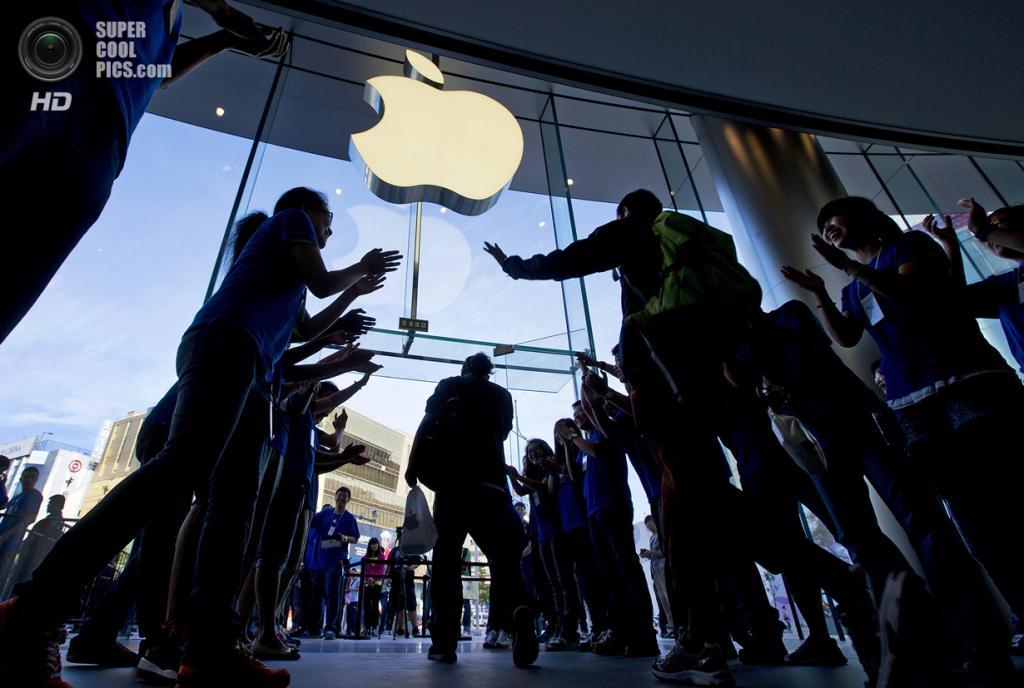 Китай. Пекин. 20 сентября. Работники Apple Store приветствуют первых покупателей. (AP Photo/Andy Wong)