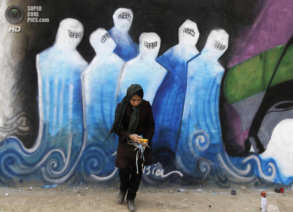 Афганистан. Кабул. 19 декабря 2010 года. Афганская художница убирает мусор перед своим граффити в промышленном парке, на котором изображена группа женщин в парандже, поднимающаяся от моря, что должно символизировать чистоту. (REUTERS/Omar Sobhani)
