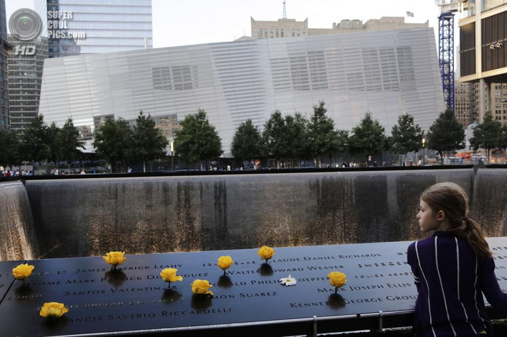 США. Нью-Йорк. 11 сентября. Восьмилетняя Шалотта Ньюман (Charlotte Newman) возложила жёлтые розы на мемориальную плиту с именами погибших 9 сентября 2001 года. (Foto AP / Mark Lennihan)