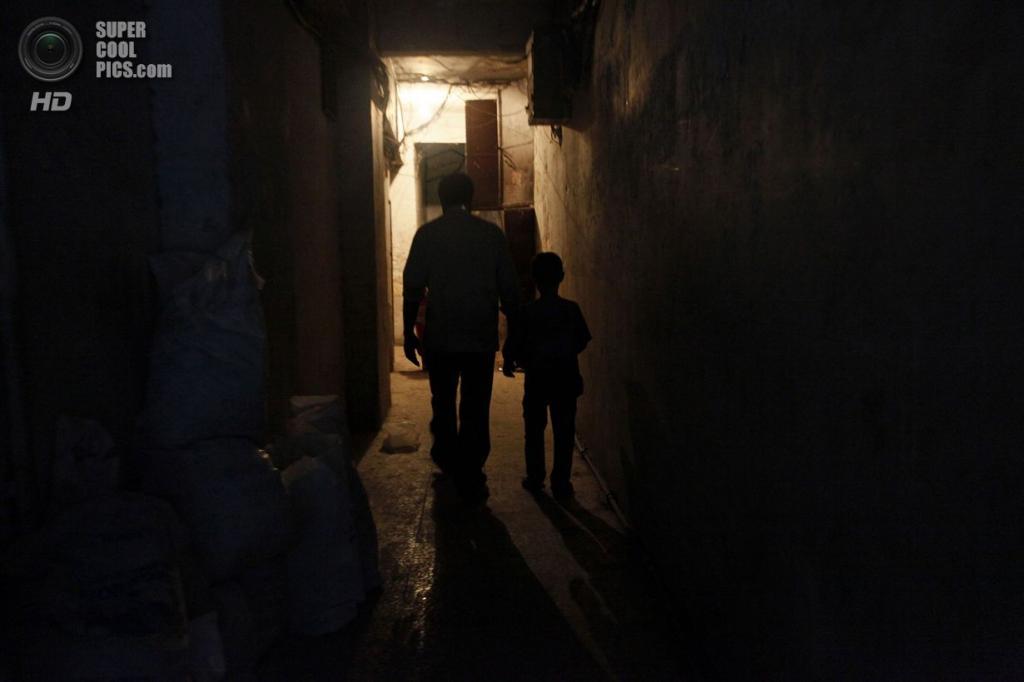 После долгого рабочего дня отец и сын возвращаются домой. (Foto Reuters / Hamid Khatib )