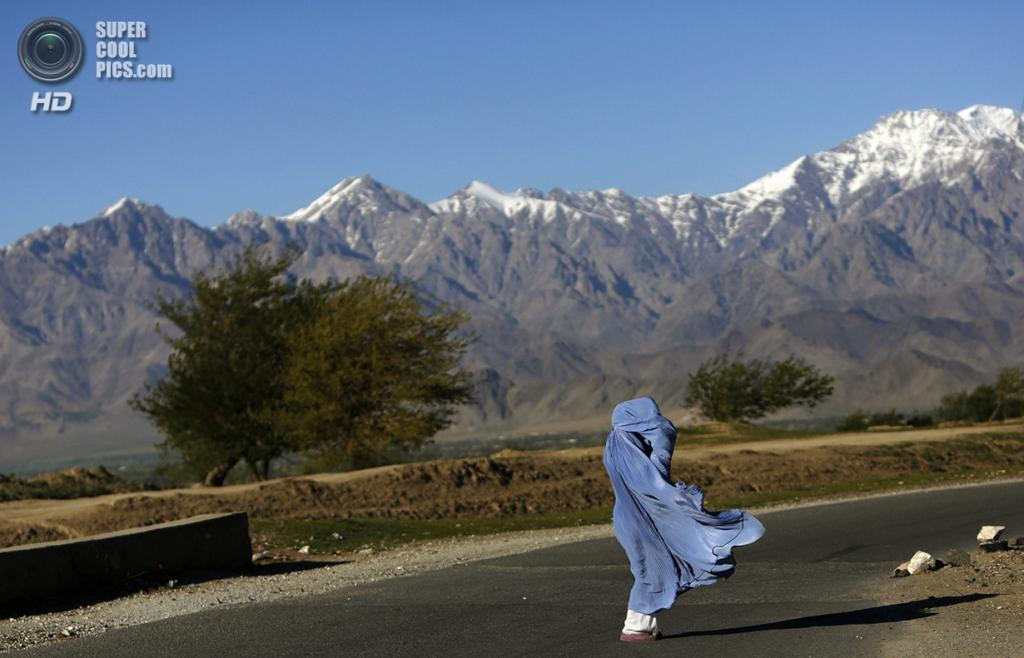 Афганистан. Кабул. 16 апреля 2013 года. Афганка в парандже идёт по просёлочной дороге в ветреный день. (REUTERS/Mohammad Ismail)