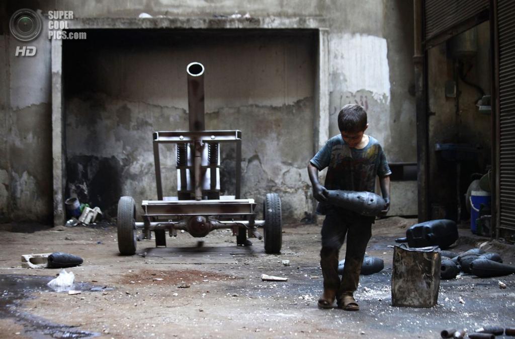 Исса ходит с миномётным снарядом по мастерской завода. (Foto Reuters / Hamid Khatib)