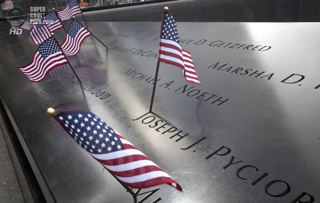 США. Нью-Йорк. 11 сентября. Национальные флаги США на мемориальной плите с именами тысяч мужчин и женщин погибших вовремя атаки 11 сентября 2001 года. (Foto Reuters / Carlo Allegri)