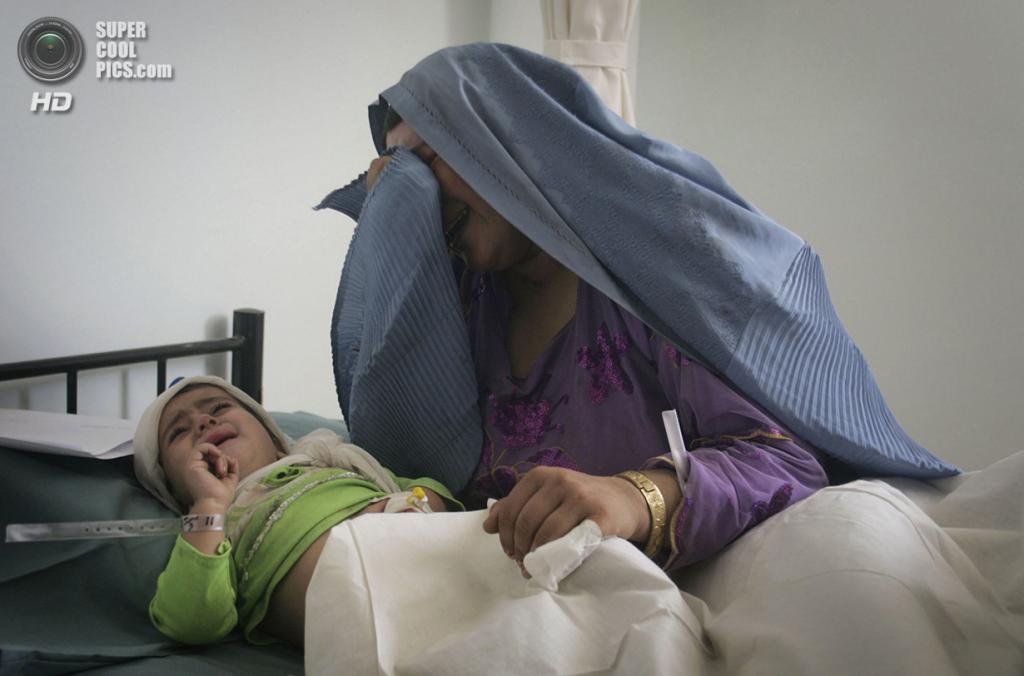 Афганистан. Герат. 18 августа 2011 года. Афганка Биби Хур плачет над своей раненой дочерью. Женщина потеряла троих детей и ещё двое были серьезно ранены во время теракта, унесшего жизни 20 человек. (AP Photo/Hoshang Hashimi)