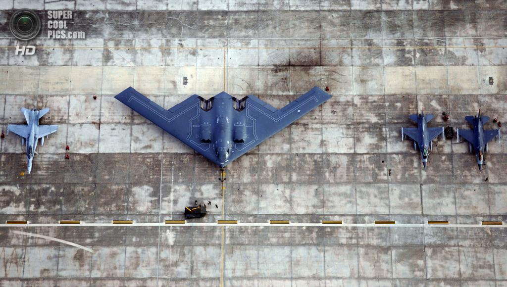 Northrop Grumman B-2 Spirit в сравнении с истребителем McDonnell Douglas F/A-18 Hornet и многоцелевыми истребителями General Dynamics F-16 Fighting Falcon. (USAF Photo/Staff Sgt Bennie J. Davis III)