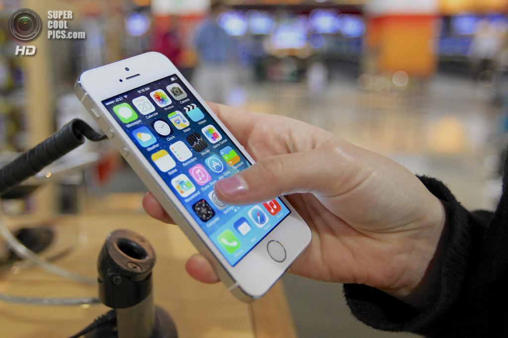 США. Омаха, Небраска. 20 сентября. Покупатель испытывает iPhone 5s в магазине Nebraska Furniture Mart. (AP Photo/Nati Harnik)