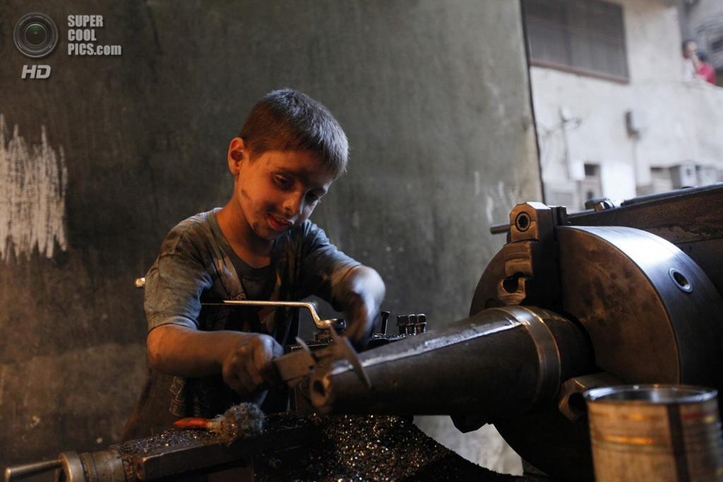 Десятилетний мальчик использует сложный рабочий инструмент и точильный станок при  изготовлении боевых снарядов. (Foto Reuters / Hamid Khatib)