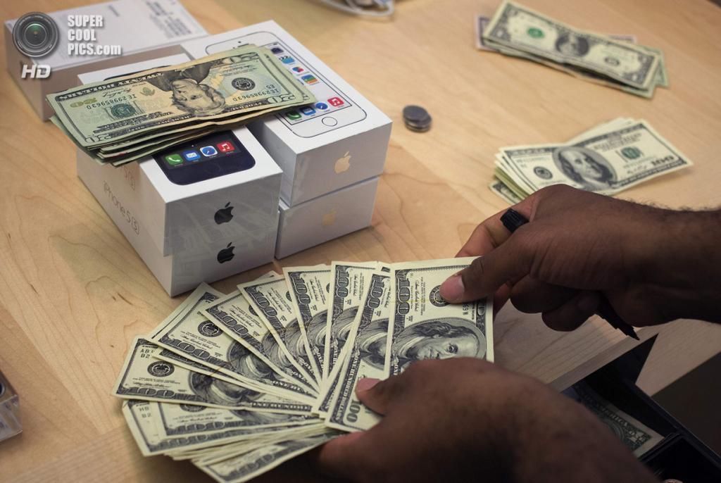 США. Нью-Йорк. 20 сентября. Кассир Apple Store пересчитывает уплаченные покупателем доллары за новый iPhone 5s. (REUTERS/Adrees Latif)