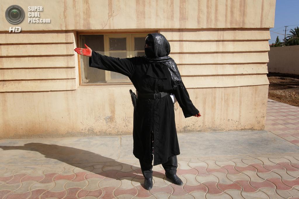 Афганистан. Лашкаргах, Гильменд. 8 марта 2010 года. Афганская женщина-полицейский указывает прохожим, не попавшим в кадр, где состоится церемония в честь Международного женского дня. (BEHROUZ MEHRI/AFP/Getty Images)