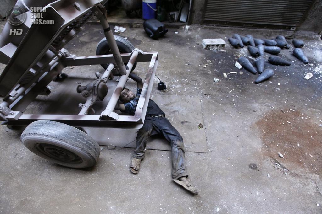 Исса ремонтирует несущую раму гранатомёта на оружейном заводе в Алеппо. (Исса вручную собирает боевые снаряды на оружейном заводе в Алеппо. (Исса проверяет исправность гранатомёта на оружейном заводе в Алеппо. (Foto Reuters / Hamid Khatib)