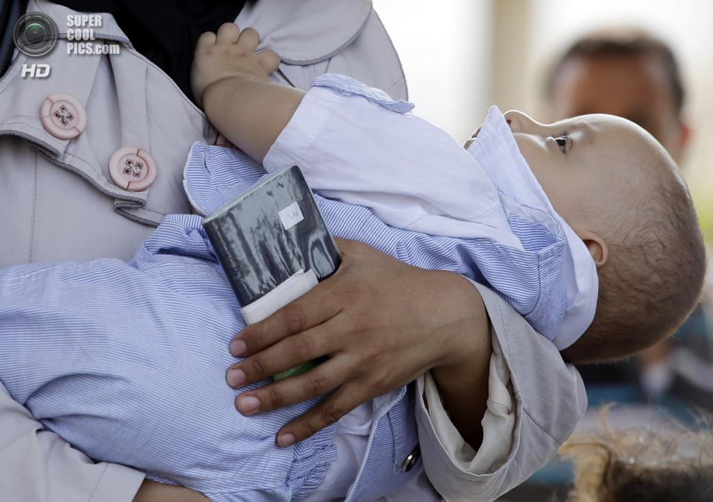 Сирийская беженка с ребенком на турецкой границе. (AP Photo/Gregorio Borgia)