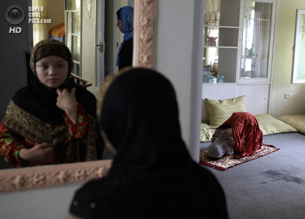 Афганистан. Кабул. 9 августа 2009 года. Мусульманка склонилась в молитве в Центре семейных рекомендаций. Согласно официальным отчетам, в Афганистане от 60 % до 80 % браков являются принудительными, 57 % невест не достигли 16-летия и 87 % — жалуется на домашнее насилие. При этом афганки являются самыми безграмотными женщинами в мире — доля грамотных не превышает 13 %. (REUTERS/Dylan Martinez)