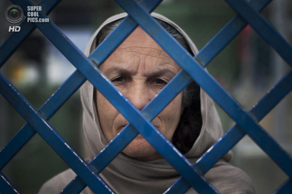Афганистан. Кабул. 28 марта 2013 года. Заключённая Фаузия выглядывает из-за решётки центральной женской тюрьмы Бадамбах. Фаузия является старейшей женщиной в тюрьме. Она отсидела уже 7 лет из 17, которые ей полагаются за убийство своего мужа и снохи. Фаузия говорит, что застукала их вместе в постели, за что и зарезала обоих. (AP Photo/Anja Niedringhaus)