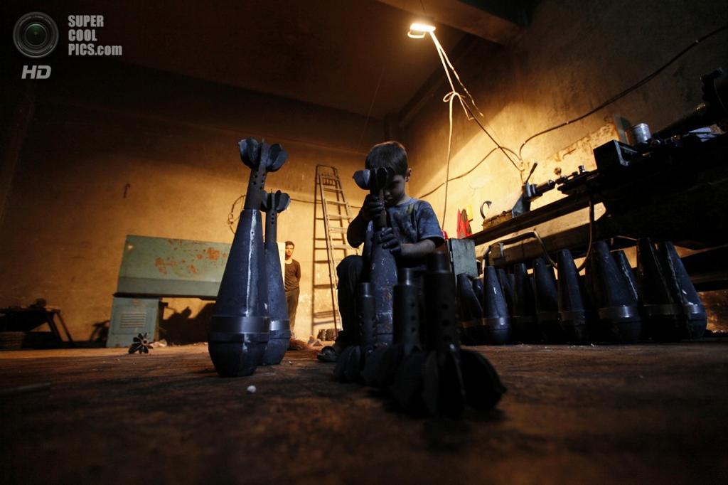 Исса вручную собирает боевые снаряды на оружейном заводе в Алеппо. (Foto Reuters / Hamid Khatib)