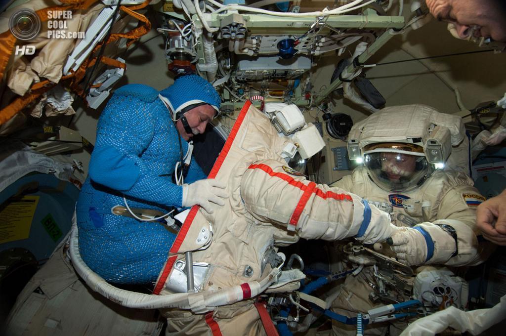 Российские космонавты Фёдор Юрчихин и Александр Мисуркин во время подготовки скафандров перед выходом в открытый космос. (NASA)