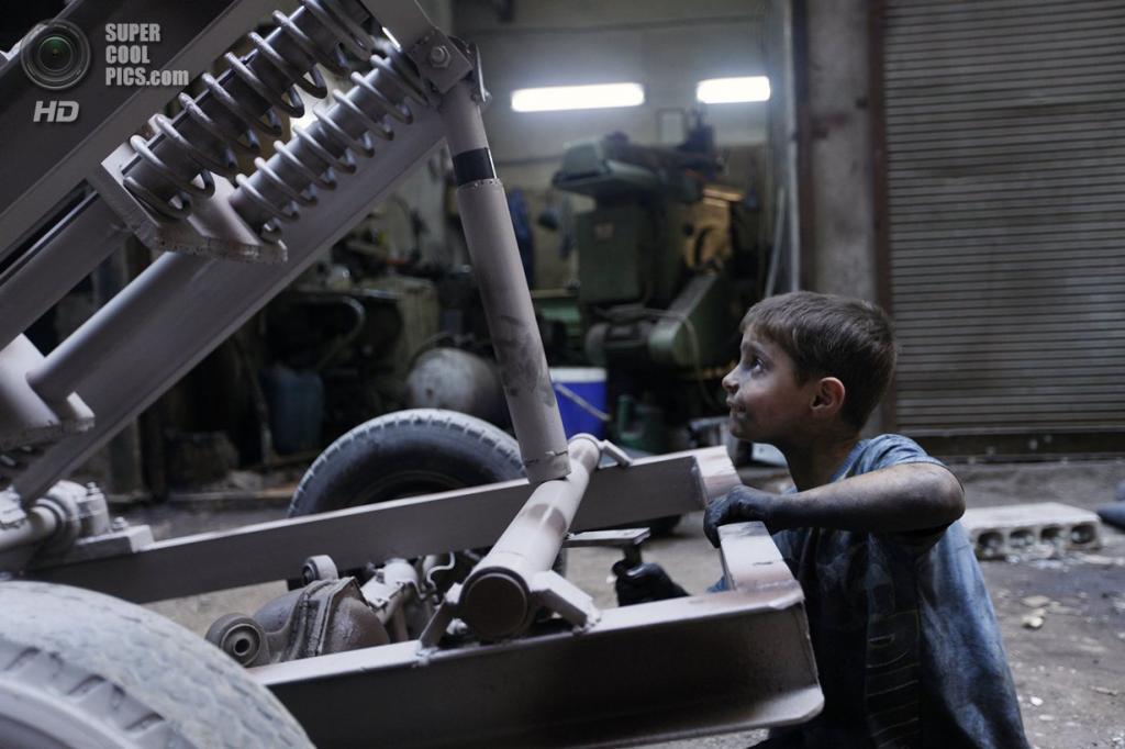 Исса проверяет исправность гранатомёта на оружейном заводе в Алеппо. (Foto Reuters / Hamid Khatib)