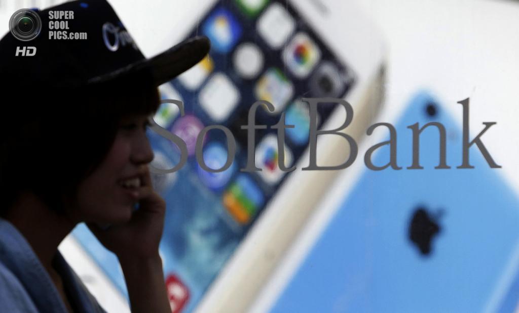 Япония. Токио. 20 сентября. Пешеход, разговаривающий по телефону, проходит постер с новыми iPhone 5s и iPhone 5c у Apple Store. (REUTERS/Yuya Shino)