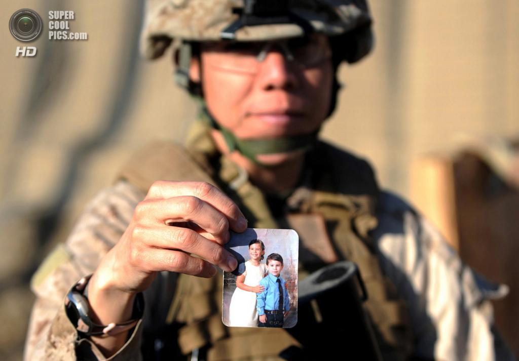 Афганистан. Гамзер, Гильменд. 20 февраля 2011 года. Сержант морской пехоты США Патриция Аквино демонстрирует на камеру помятую фотографию своих детей, Дженны и Кристофера. (ADEK BERRY/AFP/Getty Images)