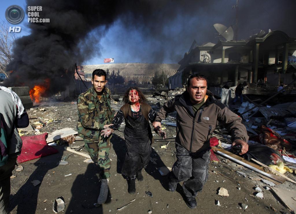 Афганистан. Кабул. 15 декабря 2009 года. Мужчины ведут пострадавшую от теракта, который был направлен против президента Афганистана Хамида Карзая. (REUTERS/Ahmad Masood)