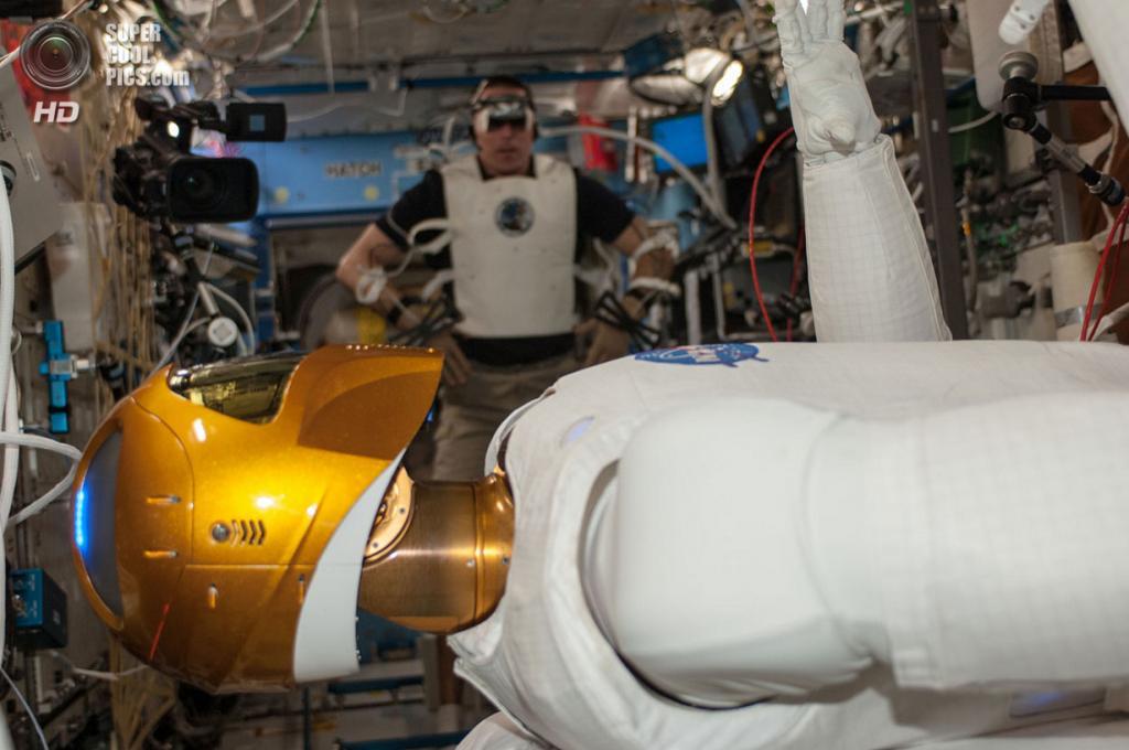 Крис Кэссиди тестирует манёвренность робота Robonaut 2 в лабораторном модуле «Дестини». (NASA)