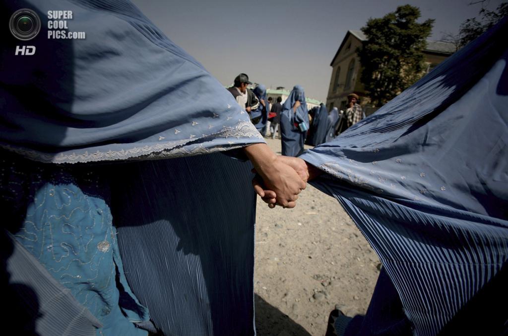 Афганистан. Кабул. 20 октября 2009 года. Две афганки в паранже, держащиеся за руки во время похода на рынок. (AP Photo/Altaf Qadri)