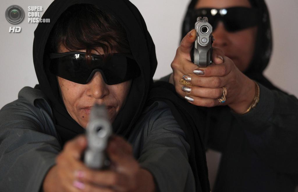 Афганистан. Кандагар. 7 июня 2010 года. Представительницы Афганской национальной полиции целятся из 9-мм пистолетов во время тренировок на стрельбище. (ED JONES/AFP/Getty Images)